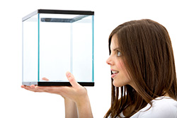 Woman wandering what to do with empty fish tank